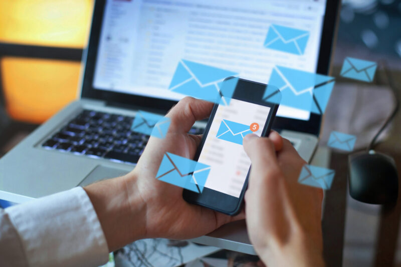 Person Using Laptop And Cell Phone Email- Healthcare Email Marketing Concept For Red Crow